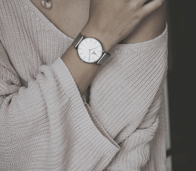 half image of woman in jumper necklace and watch